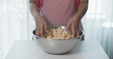persona mezclando palomitas de maíz con las manos