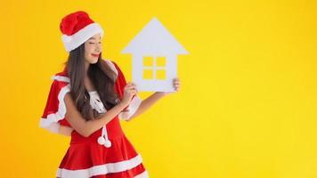 menina asiática com fantasia de Papai Noel segurando uma casa recortada em branco
