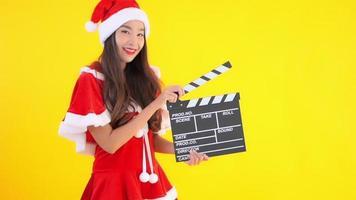 menina asiática fantasiada de Papai Noel segurando claquete