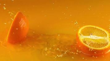 Freshly sliced orange falling in a cool water video