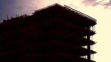 edificio sin terminar y una puesta de sol rosa