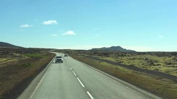 Cars Driving on Road in Iceland Near Lava Fields