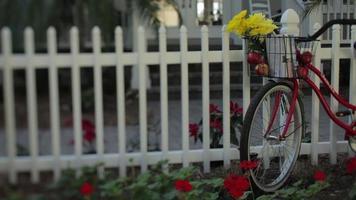 A bike on a white picket fence