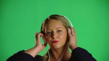 loira dançando música com fones de ouvido e clipe de estúdio
