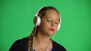 mulher loira dançando com fones de ouvido soprando seu clipe de estúdio de chiclete