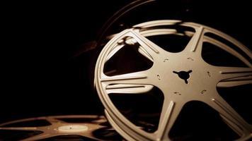 close up de arranjo de três rolos de filme antigos girando com fundo escuro em 4k