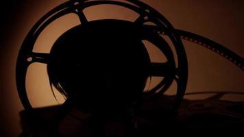 silhueta do arranjo de três rolos de filme antigos girando para a direita com iluminação quente no fundo em 4k