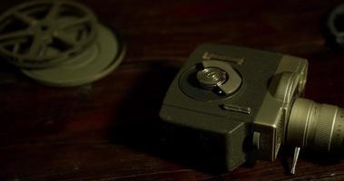 Imagem panorâmica lenta de rolos de filme e uma câmera vintage em uma mesa de madeira em 4k