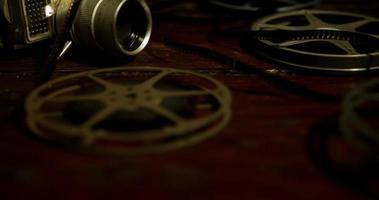 panorâmica escura na mesa indo para a esquerda dos rolos, câmera clássica e listras de filme em 4k