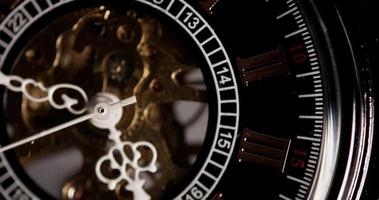 Extreme close up of pocket watch with exposed machinery coming for a minute starting in 4:45 in 4K time lapse video