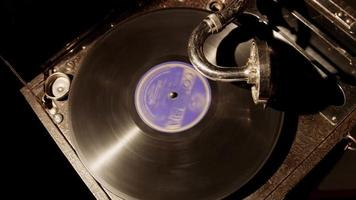 Medium static shot top view of classic music device playing a disc with purple label in 4K