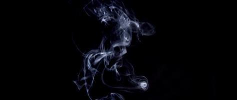 linda fumaça branca criando espirais subindo com o primeiro plano desfocado em 4k