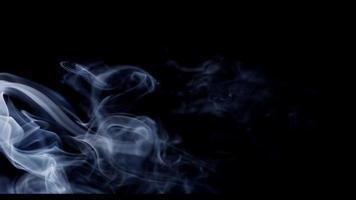 textura etérea de fumaça branca movendo-se da esquerda e desaparecendo na escuridão em 4k