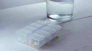 Persona que toma tres pastillas de una caja de plástico blanca.