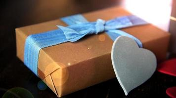 gift boxes with paper hearts on wood table close up video
