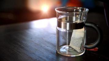 chá sendo servido em uma xícara de chá de vidro