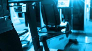 una niña haciendo ejercicio en una bicicleta estática en un gimnasio.