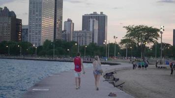 Pareja caminando sobre un muelle de Chicago con edificios en segundo plano.