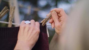 Extremo cerca de la mano de la vieja dama colocando pinzas para la ropa