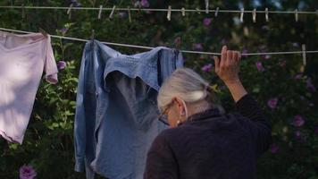 clip palmare della vecchia signora che prende i vestiti dal suo cesto della biancheria