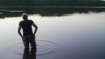 foto média de uma senhora no lago olhando a floresta video