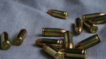 Disparo giratorio cinematográfico de balas sobre una superficie de tela - balas 083