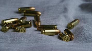 Disparo giratorio cinematográfico de balas sobre una superficie de tela - balas 082