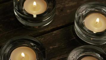Velas de té con mechas en llamas sobre un fondo de madera - velas 002