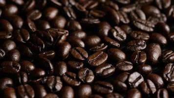 Foto giratoria de deliciosos granos de café tostados sobre una superficie blanca - granos de café 016