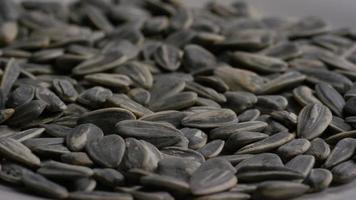 ripresa cinematografica e rotante di semi di girasole su una superficie bianca - semi di girasole 019 video
