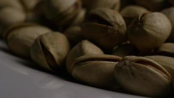 Cinematic, rotating shot of pistachios on a white surface - PISTACHIOS 043