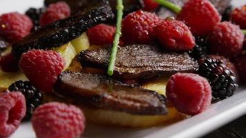 colpo rotante di un delizioso piatto di pancetta affumicata d'anatra con ananas grigliato, lamponi, more e miele - cibo 103