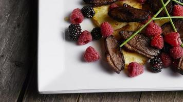 Foto giratoria de un delicioso plato de tocino de pato ahumado con piña asada, frambuesas, moras y miel - comida 110