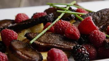 Foto giratoria de un delicioso plato de tocino de pato ahumado con piña asada, frambuesas, moras y miel - comida 104