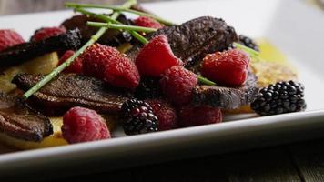 Plan rotatif d'un délicieux plat de bacon de canard fumé avec ananas grillé, framboises, mûres et miel - nourriture 102