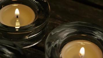 Velas de té con mechas en llamas sobre un fondo de madera - velas 017