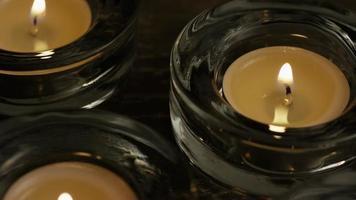 Velas de té con mechas en llamas sobre un fondo de madera - velas 016