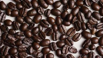 Foto giratoria de deliciosos granos de café tostados sobre una superficie blanca - granos de café 030