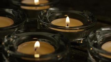 Velas de té con mechas en llamas sobre un fondo de madera - velas 019