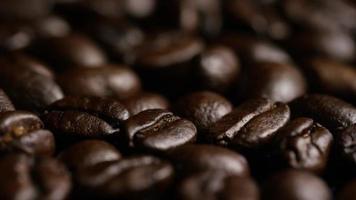 Foto giratoria de deliciosos granos de café tostados sobre una superficie blanca - granos de café 025