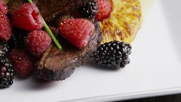 tomada rotativa de um delicioso prato de bacon de pato defumado com abacaxi grelhado, framboesas, amoras e mel - comida 106 video