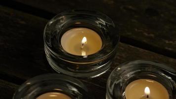 Velas de té con mechas en llamas sobre un fondo de madera - Velas 025