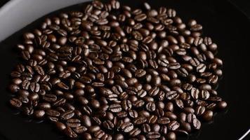 Foto giratoria de deliciosos granos de café tostados sobre una superficie blanca - granos de café 011