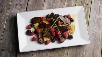 colpo rotante di un delizioso piatto di pancetta affumicata d'anatra con ananas grigliato, lamponi, more e miele - cibo 090