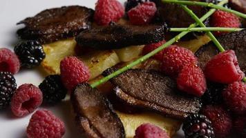 tomada rotativa de um delicioso prato de bacon de pato defumado com abacaxi grelhado, framboesas, amoras e mel - comida 117 video