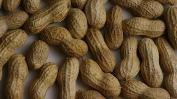 filme cinematográfico giratório de amendoim em uma superfície branca - amendoim 004