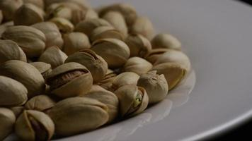 Cinematic, rotating shot of pistachios on a white surface - PISTACHIOS 040