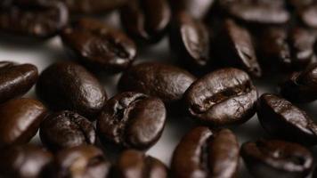 Foto giratoria de deliciosos granos de café tostados sobre una superficie blanca - granos de café 045
