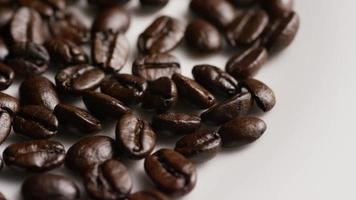 Foto giratoria de deliciosos granos de café tostados sobre una superficie blanca - granos de café 042
