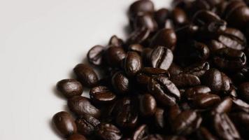 Foto giratoria de deliciosos granos de café tostados sobre una superficie blanca - granos de café 070